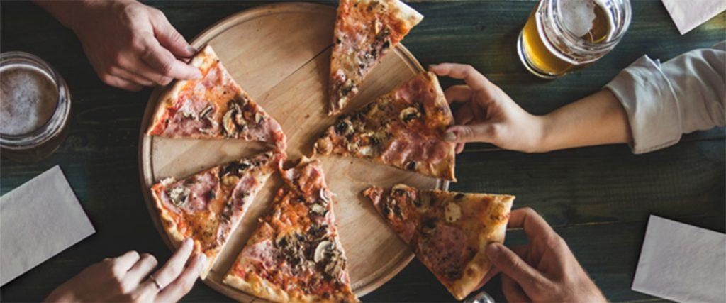 a photo of people grabbing slices of pizza and using commercial napkins.