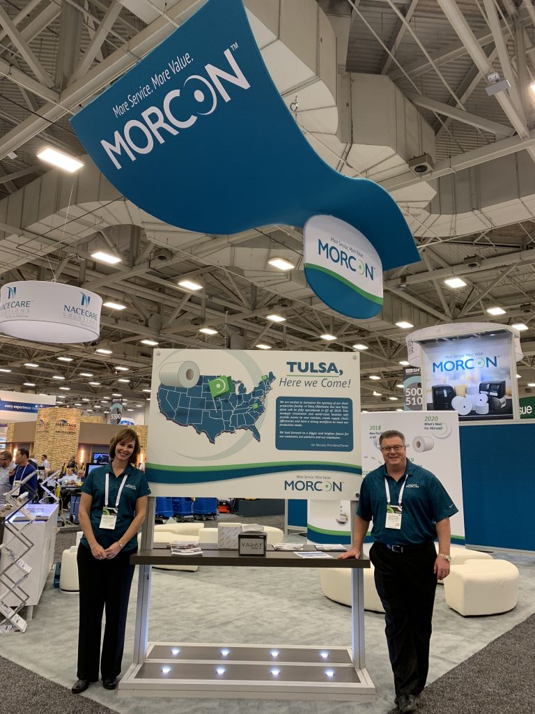 Morcon Tissue's Booth at ISSA with Joe Raccuia and Laura Morris posing by the new Tulsa location sign
