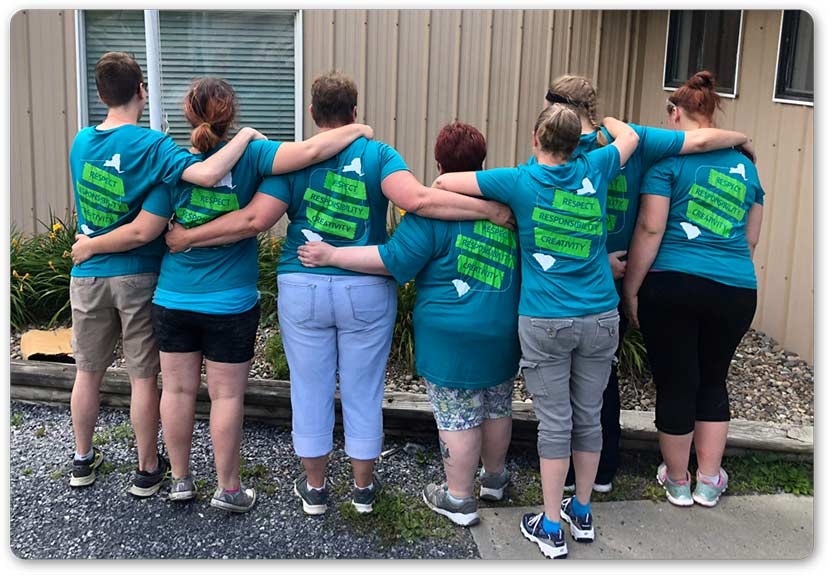 Morcon employee's showing off the back of their company t-shirts